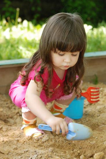 Kind mit Spielsand und Sandspielzeug