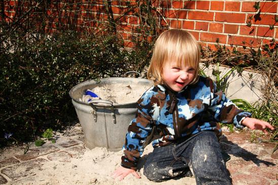 Kind spielt mit Sand in einer Zinkwanne